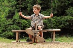 Un volo del ragazzo su un'oscillazione piana di legno in parco Fotografia Stock