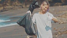 Un volontario su una spiaggia nera dell'oceano con rifiuti di plastica in una borsa nera, mostra una mano come il segno Riordinan video d archivio