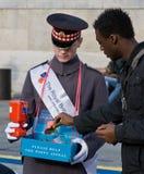 Un voluntario que vende amapolas el día de armisticio Foto de archivo libre de regalías