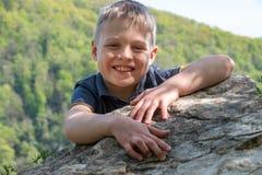 Un voyageur de garçon avec un sourire monté jusqu'au dessus de la falaise photographie stock