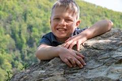 Un voyageur de garçon avec un sourire monté jusqu'au dessus de la falaise image libre de droits