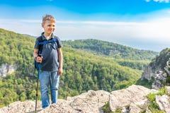 Un voyageur de sourire de gar?on avec des poteaux de trekking et un sac ? dos se tient sur une montagne parmi une for?t verte photo stock
