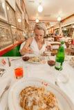 Un voyageur féminin s'assied dans un restaurant sur l'île de Burano et va manger de ses pâtes avec des coquillages photographie stock