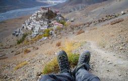 Un voyageur solo avec des chaussures de trekking avec le monastère principal à l'arrière-plan Images libres de droits