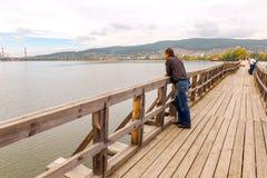 Un voyageur sur un pont en bois piétonnier à travers l'étang de Beloretsk photos stock