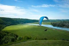 Un vuelo del ala flexible en el cielo azul contra la perspectiva de las nubes Paragliding en el cielo en un día soleado imagen de archivo libre de regalías
