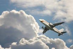 Un vuelo del avión de pasajeros en el cielo nublado Fotografía de archivo libre de regalías