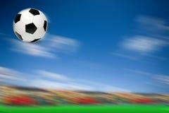 Un vuelo del balón de fútbol Imágenes de archivo libres de regalías