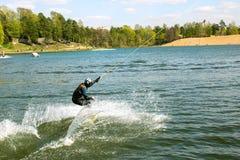 Un wakeboarder in galleggianti di una tuta su un wakeboard che spruzza acqua sul lago in parco immagine stock libera da diritti