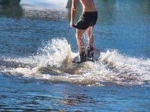 Un wakeboarder, hombre joven en paseos de un wakeboard en el agua en pantalones cortos sin una camiseta fotografía de archivo libre de regalías