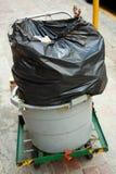 Un wheelie-coffre avec un sac de détritus en plastique noir Images stock