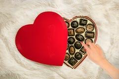 Un woman& x27; mano de s que alcanza para un caramelo de chocolate Fotos de archivo libres de regalías