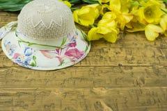 Un woman& x27; sombrero de s del sol y de la tabla rústica de los tulipanes Imagen de archivo libre de regalías
