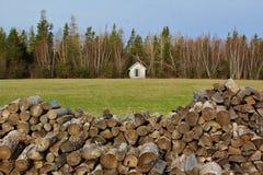 Un woodpile con un prado, un bosque, y una cabina en el fondo Fotos de archivo