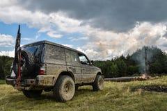 Un 4x4 sale SUV tous terrains s'est garé avant un feu de camp Photographie stock