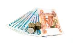 Un y cinco mil rublos de billetes de banco y una y diez rublos de monedas aisladas en el fondo blanco Fotos de archivo libres de regalías