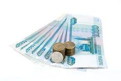 Un y cinco mil rublos de billetes de banco y una y diez rublos de monedas aisladas en el fondo blanco Imagenes de archivo
