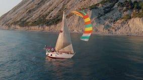 Un yacht bianco sotto una vela bianca con una squadra naviga tranquillamente lungo il mare blu lungo una riva montagnosa stock footage