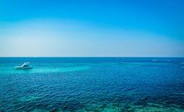 Un yacht blanc minuscule au milieu de la mer image stock