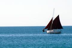 Un yacht solitaire avec les voiles foncées Image stock
