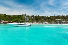Un yacht sotto il cielo blu contro una spiaggia tropicale Immagine Stock