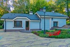 Un yard propre et spacieux avec un lit de fleur devant la maison sur le fond de la colline photographie stock
