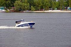 Un yate de la excursión nada rio abajo junto con la costa Fotografía de archivo