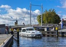 Un yate del motor pasa el puente rotatorio en la ciudad del malchow en Brandeburgo imagen de archivo