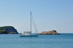 Un yate en el mar adriático y la isla rocosa Imagen de archivo libre de regalías