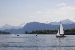 Un yate está navegando en el agua Ciudad suiza montañas hermosas El cielo hermoso Agua azul imagen de archivo