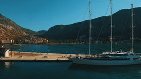 Un yate grande se coloca en el embarcadero en la bahía Kotor, Montenegro Cantidad aérea metrajes