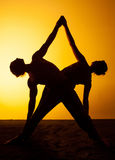 Un'yoga di pratica di due genti alla luce di tramonto Fotografie Stock Libere da Diritti