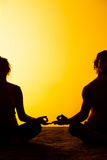 Un'yoga di pratica di due genti alla luce di tramonto Fotografia Stock Libera da Diritti