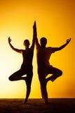 Un'yoga di pratica di due genti alla luce di tramonto Immagine Stock Libera da Diritti