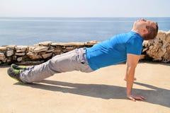 Un'yoga di pratica, i pilates e un allungamento del giovane su una spiaggia L'uomo bello sta facendo allungando gli esercizi sull Fotografie Stock