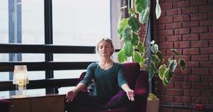 In un'yoga di progettazione di signora moderna ed urbana del posto a casa la meditazione di pratica posa di mattina sul sofà che  stock footage