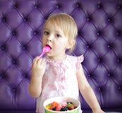 Un yogourt glacé de consommation de jeune fille Image stock