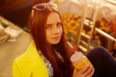 Un zumo de naranja adolescente pelirrojo de las bebidas Fotos de archivo