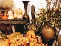 Una aún-vida con las calabazas con el jarro arrugado de la arcilla de la pimienta y un jarro del metal con los ornamentos acuñado Fotos de archivo
