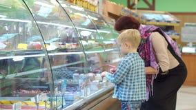 Una abuela con un peque?o nieto en la tienda elige los dulces en el contador almacen de metraje de vídeo