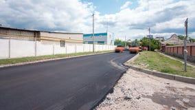 Una acabadora de la pavimentadora, acabadora del asfalto o máquina de pavimentación que coloca una capa de asfalto durante un pro almacen de video