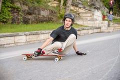 Una acción joven del individuo hace una diapositiva en un longboard en el centro turístico de la ciudad Fotos de archivo libres de regalías
