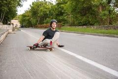 Una acción joven del individuo hace una diapositiva en un longboard en el centro turístico de la ciudad Fotografía de archivo