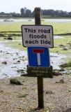 Una advertencia de la muestra contra el estacionamiento del coche en un camino que inunda con cada alta marea Imagen de archivo