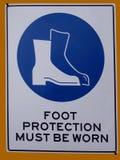 Una advertencia de la muestra del peligro que la protección se debe llevar para los pies e Fotos de archivo