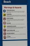 Una advertencia de la playa y una muestra de peligros con regulaciones Fotografía de archivo