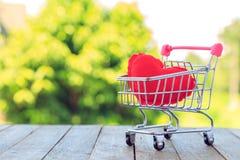 Una almohada roja del corazón en mini carro de la compra en la tabla de madera Fotografía de archivo libre de regalías