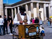 Una amoladora de órgano tradicional por la puerta de Brandeburgo es el ` s de Berlín la mayoría de la señal famosa Foto de archivo libre de regalías
