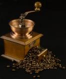 Una amoladora de café pasada de moda con los granos de café Fotos de archivo