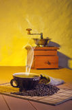 Una amoladora de café y una taza de café Fotos de archivo